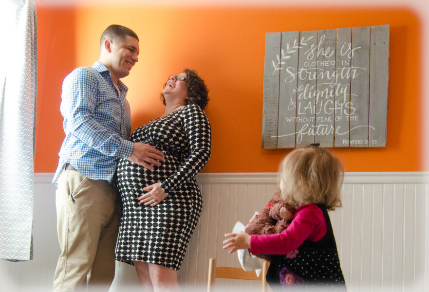 a portrait of a pregnant mom and dad laughing while young daughter looks on